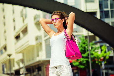 young  woman with  sunglasses out in the city hot summer day Stock Photo