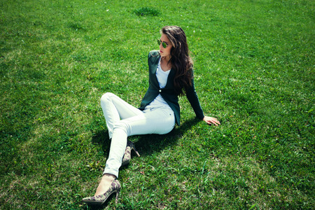 white pants: elegant young woman with sunglasses, green jacket,  white pants and high heel shoes sit on grass in park, full body shot