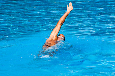 backstroke: young man swim backstroke style in outdoor swimming pool, sunny summer day