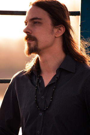 man with long hair: young beard man with long hair in shirt  portrait at sunset, profile Stock Photo