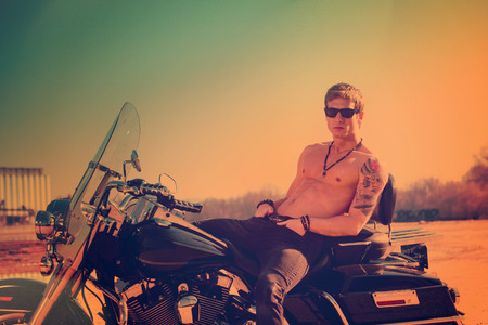 handsome muscular young man on a motorcycle summer day at sunset , retro colors