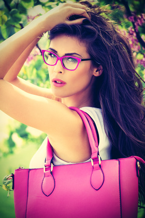 市ピンク ファッション アクセサリーを持つ若い女性。バッグ、眼鏡、公園内屋外