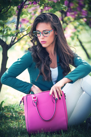 city young woman with fashion accessories. bag and eyeglasses, outdoor in park Stock Photo