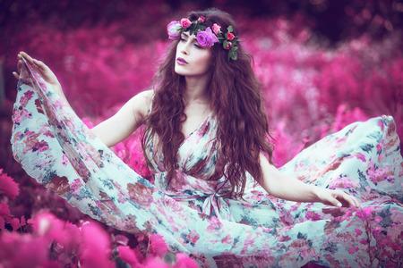 非現実的なピンク フィールドに花柄のドレスを舞う美しい遊び心のある妖精女