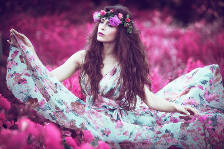 tales: beautiful playful fairy  woman in fluttering floral dress in unreal pink field