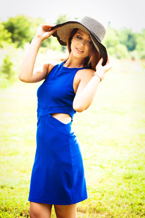 look latino: smiling young woman in blue short dress and hat, outdoor shot, summer day Stock Photo