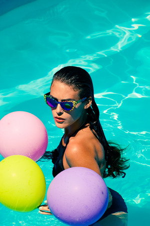 float: young attractive woman with sunglasses and balloons in the  pool