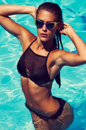 gafas de sol: joven atractiva mujer curtida en bikini negro y gafas de sol en la piscina