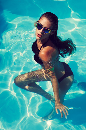 charming: tanned young attractive woman in black bikini and sunglasses in pool