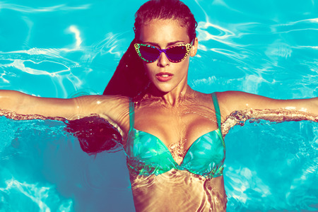 tanned: young attractive woman in  in pool with sunglasses  above view Stock Photo