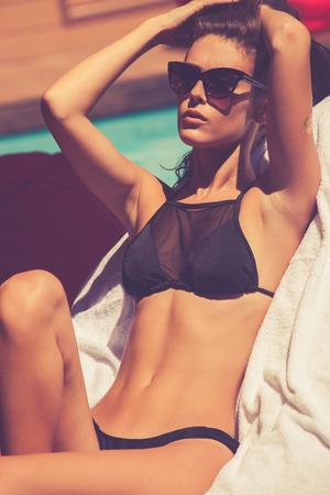 bikinis: young tanned woman in black bikini enjoy in sunbath at pool