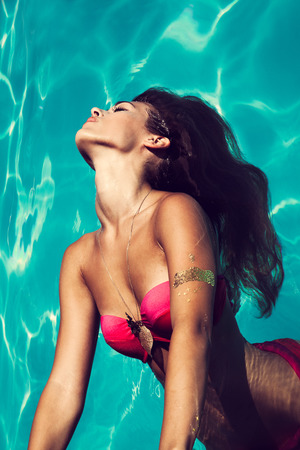 pool side: young attractive woman in  in pool with head thrown back above view