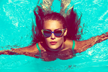 fresh face: young attractive woman swimm in  pool with sunglasses