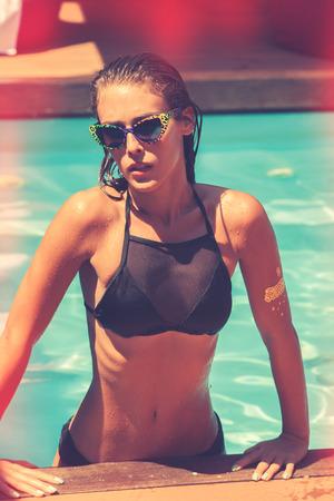 swimm: tanned young attractive woman in black bikini and sunglasses in pool