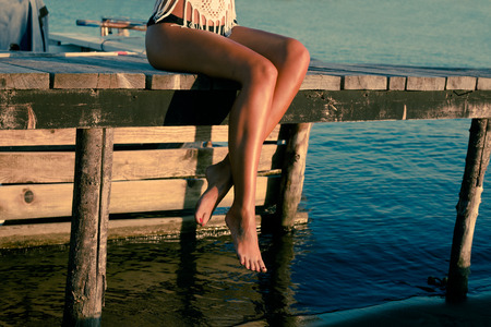 barefoot woman sit on sea dock relaxing summer day at sunset
