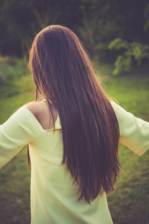 back straight: young woman with long straight hair, back shot, outdoor in park, retro colors Stock Photo