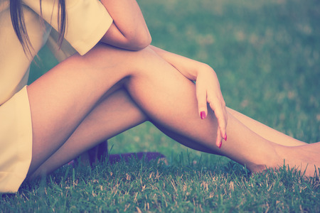 human leg: barefoot female legs in grass retro colors
