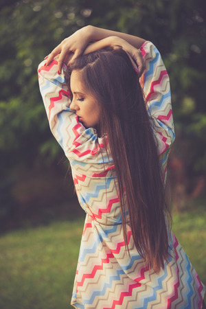 hair back: young woman in retro look hippie dress outdoor in nature