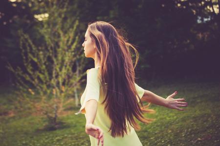 夏の風を自然の中で若い女性を楽しむ