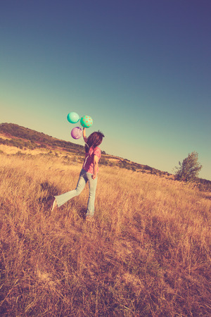 upland: woman in casual clothes run on upland with balloons in hand, full body shot, summer day retro colors