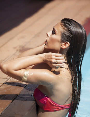 hot day: beautiful brunette at the edge of pool Stock Photo