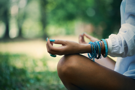 woman meditate  in wood, close up of legs, hands and part of body in white shirt, selective focus on hand, side view Stock Photo