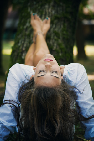backwards: woman relax in nature, legs lean on tree, head thrown backwards, eyes closed, selective focus, natural light