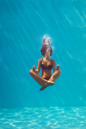 free diving: young woman in black bikini in yoga position underwater in diving aquarium, full body shot, front view through the glass