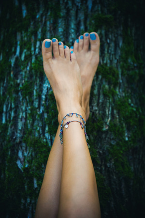 young feet: barefoot woman feet with ankle bracelets lean on tree with moss, natural light, selective focus