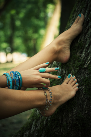 cuffs: barefoot female feet and hand with boho style bracelets and ring, lean on tree, closeup, selective focus Stock Photo