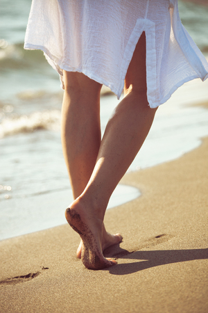 lower body: barefoot woman walk down sand beach by the sea in white long shirt, lower body, selective focus Stock Photo