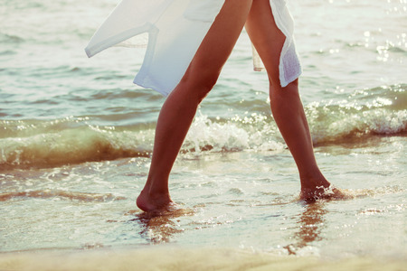 long feet: barefoot woman walk through sea water on sandy beach in white long shirt, lower body, selective focus, side view Stock Photo
