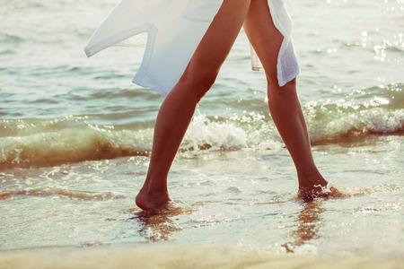 pieds nus femme: femme aux pieds nus marcher dans l'eau de mer sur la plage de sable blanc longue chemise, le bas du corps, mise au point s�lective, vue de c�t�