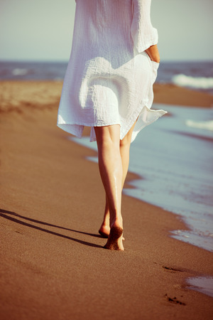 lower body: barefoot woman walk down sand beach by the sea in white long shirt, lower body, selective focus, back view