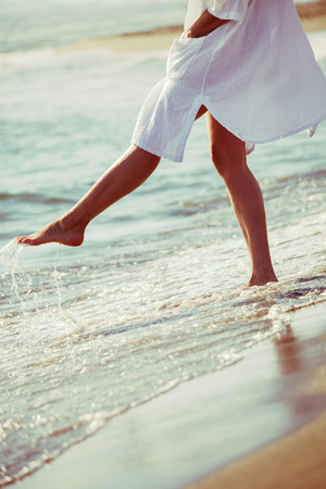 lower body: barefoot woman enjoy in sea water in white long shirt, lower body, selective focus, side view