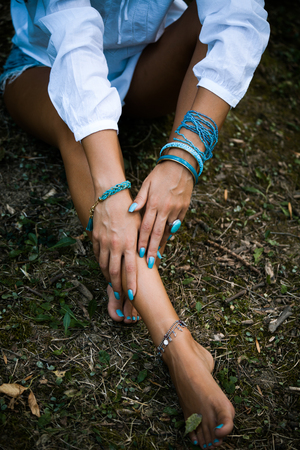 knack: young woman hands and barefoot legs with lot of turquoise bijou, above view, natural light, selective focus