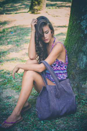 leather bag: young beautiful woman sit by tree in park wearing purple print top and big leather bag, full body shot Stock Photo