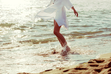 tanned body: barefoot woman enjoy in sea water in white long shirt, lower body,  side view
