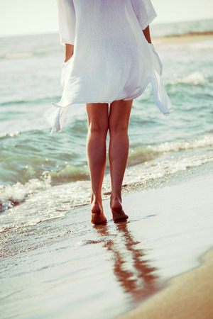 view woman: barefoot woman enjoy in sea water on sandy beach in white long shirt, lower body, back view