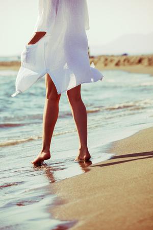 lower body: barefoot woman enjoy in sea water on sandy beach in white long shirt, lower body, back view