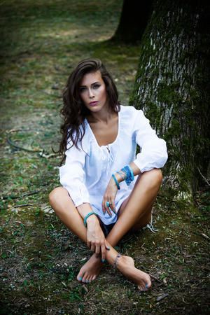 beautiful young barefoot woman in white shirt and jeans shorts sit by  tree in park, look at camera, natural light, full body shot