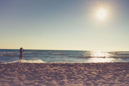 mujer mirando el horizonte: mujer en bikini de pie en la playa de arena mirando el horizonte, día soleado de verano, vista posterior, colores retro, Ada Bojana, Montenegro Foto de archivo