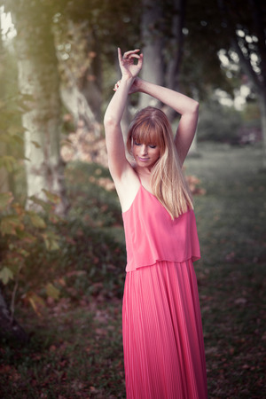 arms up: young grace beautiful blonde woman in pink dress outdoor shot in wood with arms up Stock Photo