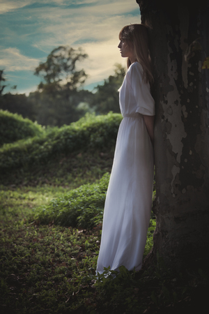 forest wood: young woman in long white dress lean against big tree looking far away, full body shot, profile, summer day