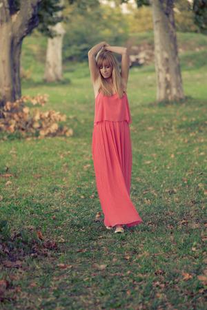 giovane donna bionda in abito lunga passeggiata nella natura tra alberi, spensierata e felice, colpo di corpo pieno, colori retrò
