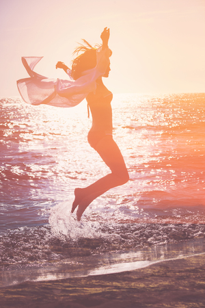 jumps: double exposure of a woman jumping against sea at sunset
