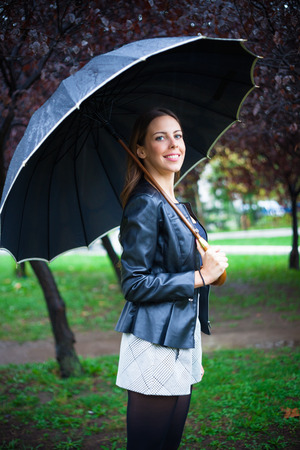 autmn: smiling beautiful  young woman under umbrella outdoor shot, rainy autmn day in the city park