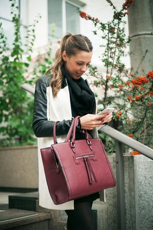 bajando escaleras: mujer joven sonriente en el impermeable que va a bajar las escaleras, llevando el bolso y el teléfono inteligente en la mano, los mensajes de texto de masaje, tiro al aire libre en la ciudad, día lluvioso, el enfoque selectivo