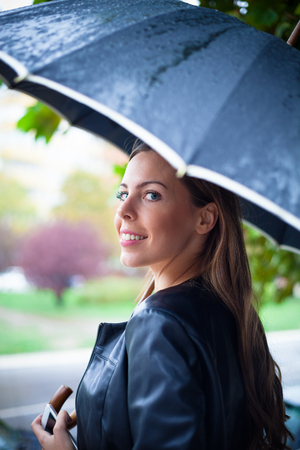 autmn: young smiling woman under umbrella in the city, cold rainy autmn day Stock Photo