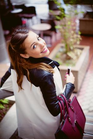 bajando escaleras: mujer joven sonriente en el impermeable que va a bajar las escaleras, mirando hacia atrás en la cámara, con el bolso y el teléfono inteligente en la mano, tiro del día al aire libre en la ciudad, día lluvioso, el enfoque selectivo Foto de archivo